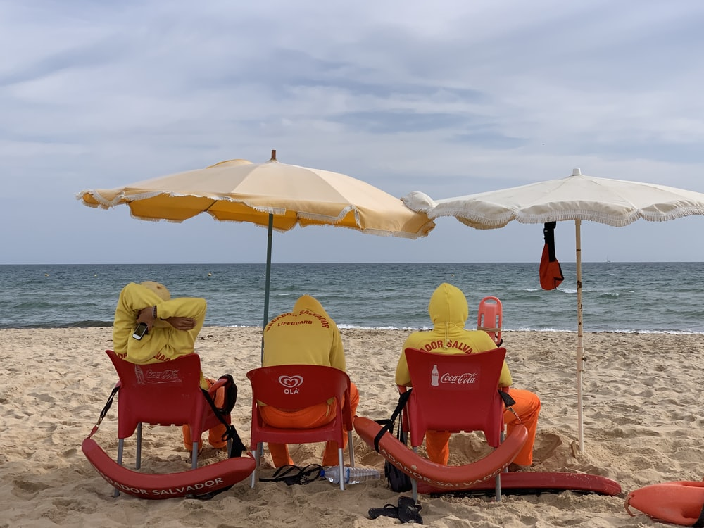 three persons sitting on chairs under parasols at the sand seashore during day