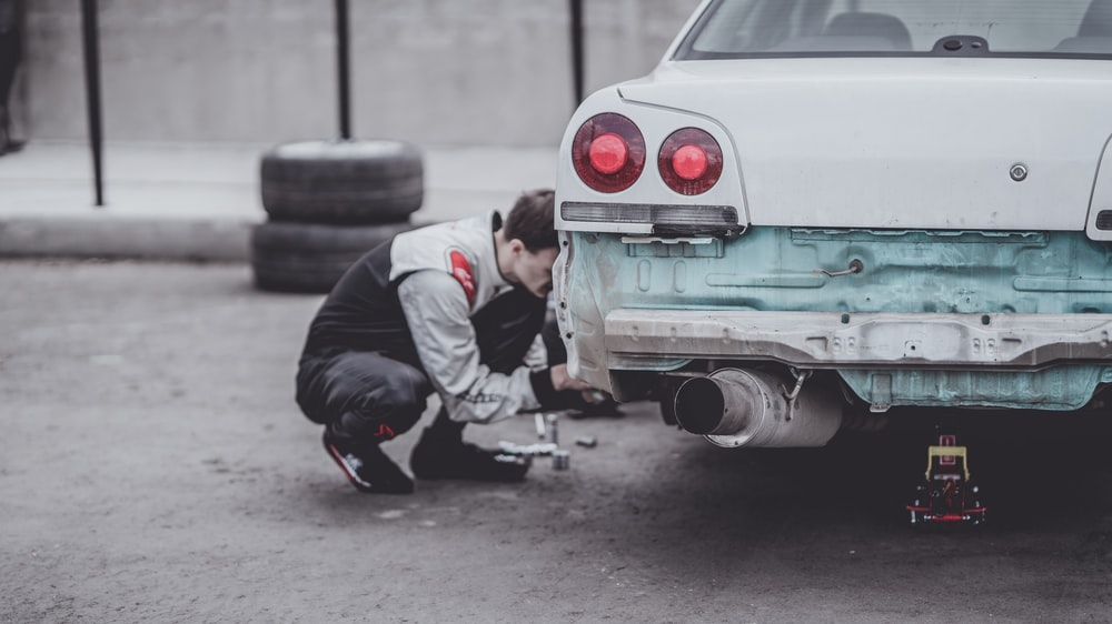 man fixing car