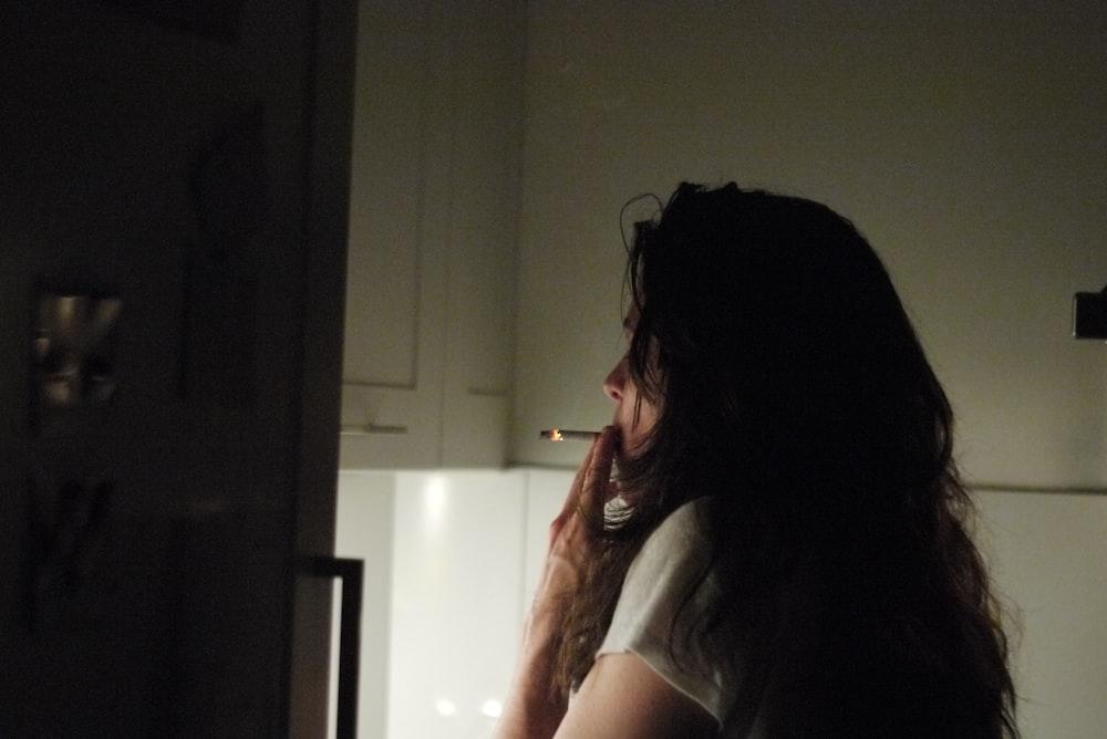 woman wearing white shirt smoking