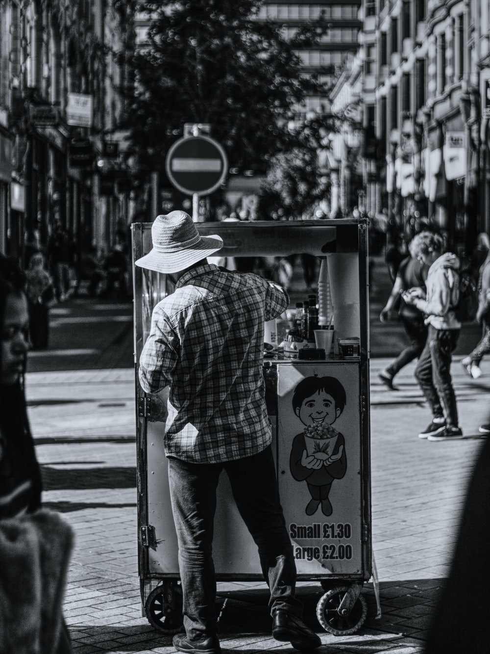 grayscale photography of man selling popcorns