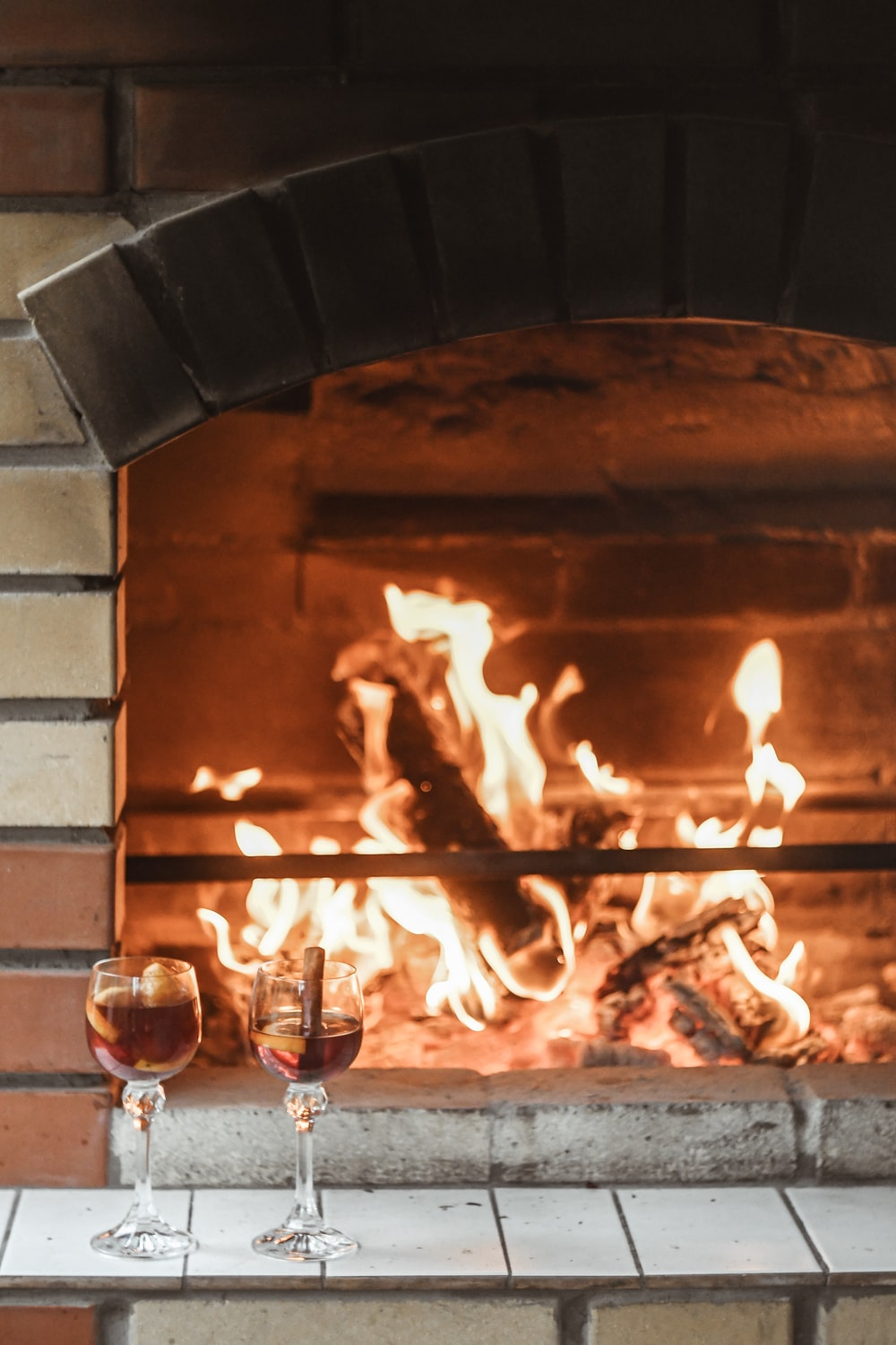 two filled wine glasses near fireplace