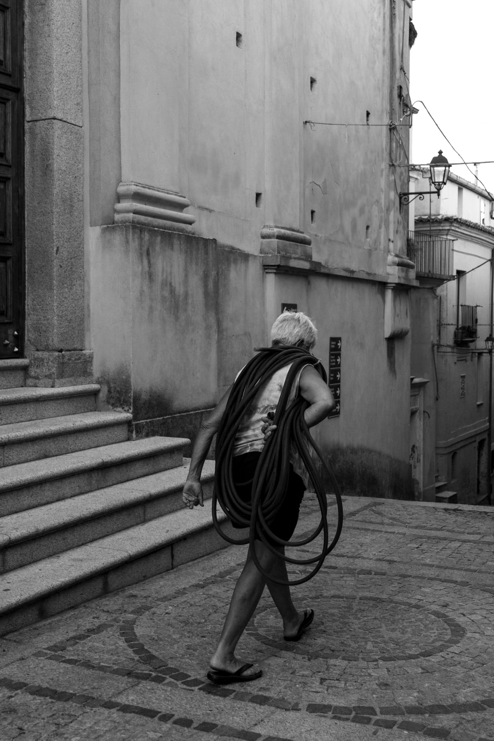 woman carrying rope walking near stairs