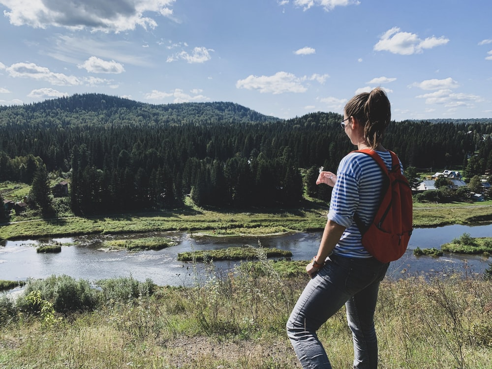 woman with red backpack facing and standing in green field viewing river and mountain under blue and white skies during daytime