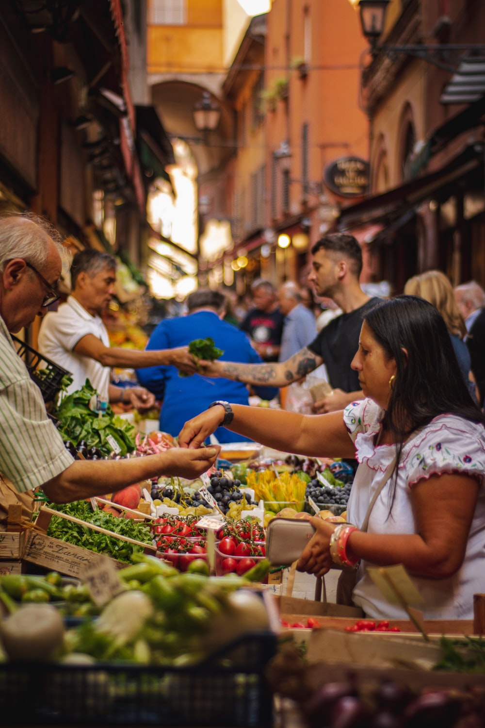 woman wearing white and red blouse buying some veggies