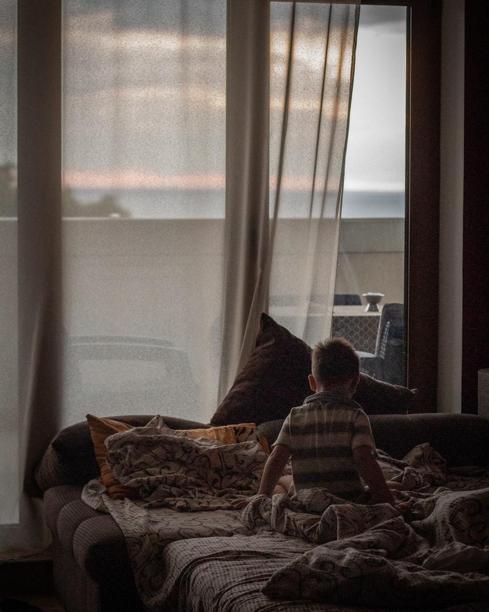 boy on bed near window