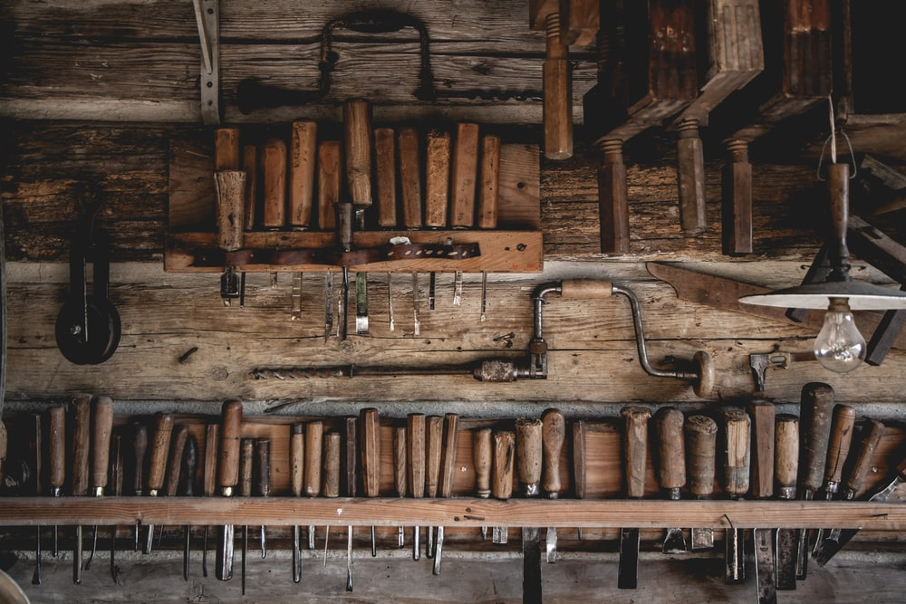 brown wooden chisel set on display near different carpentry tools