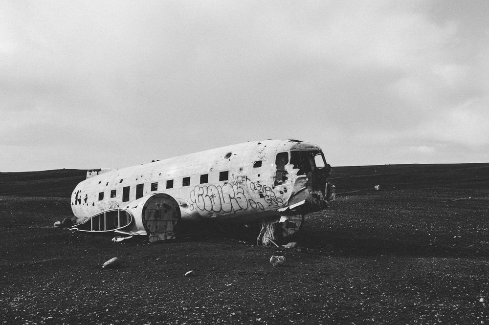 grayscale photography of abandoned and destroyed airplane on ground