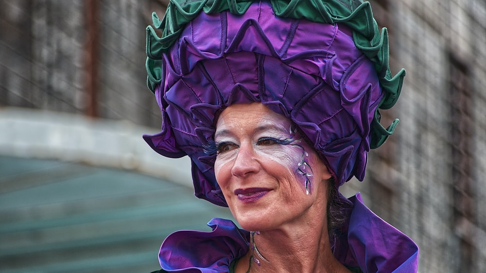 focus photography of woman in purple hat