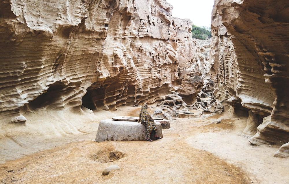 person sitting on rock between rock walls