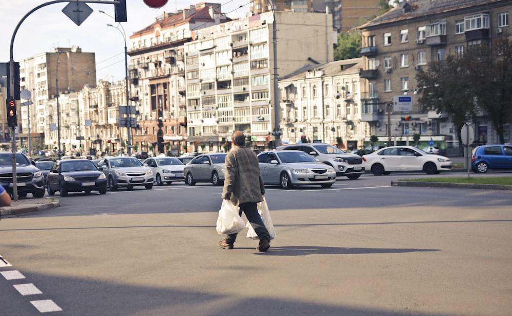 person wearing beige jacket walking on street