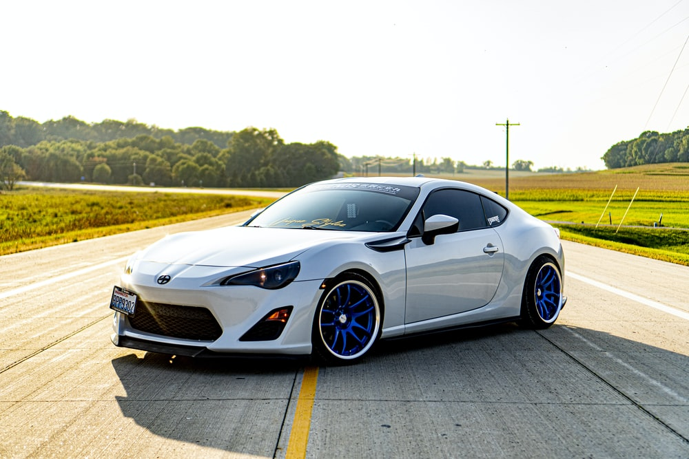 white sports coupe on road