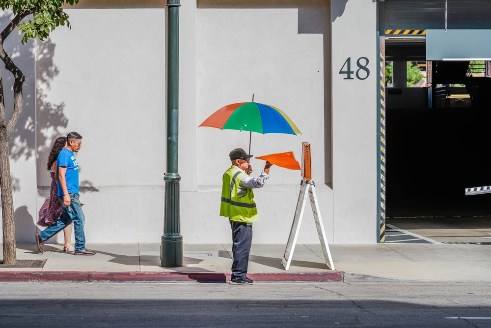 man holds multicolored umbrella near number 48 building
