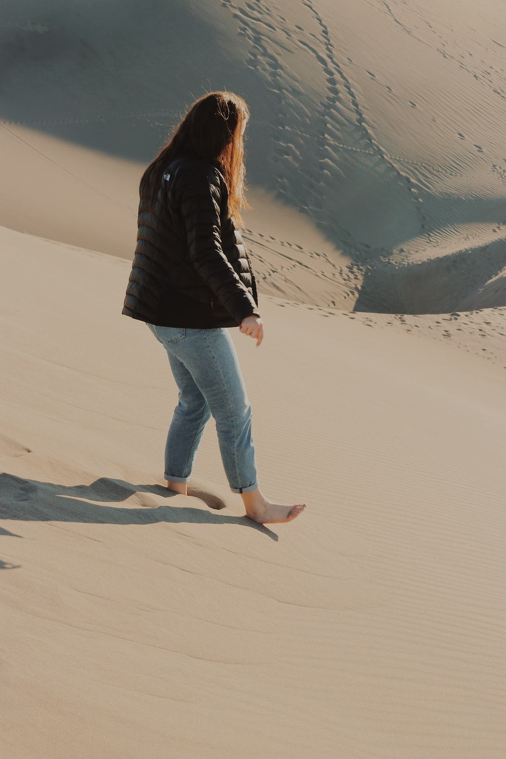 barefoot naked woman with jacket on sand dunes