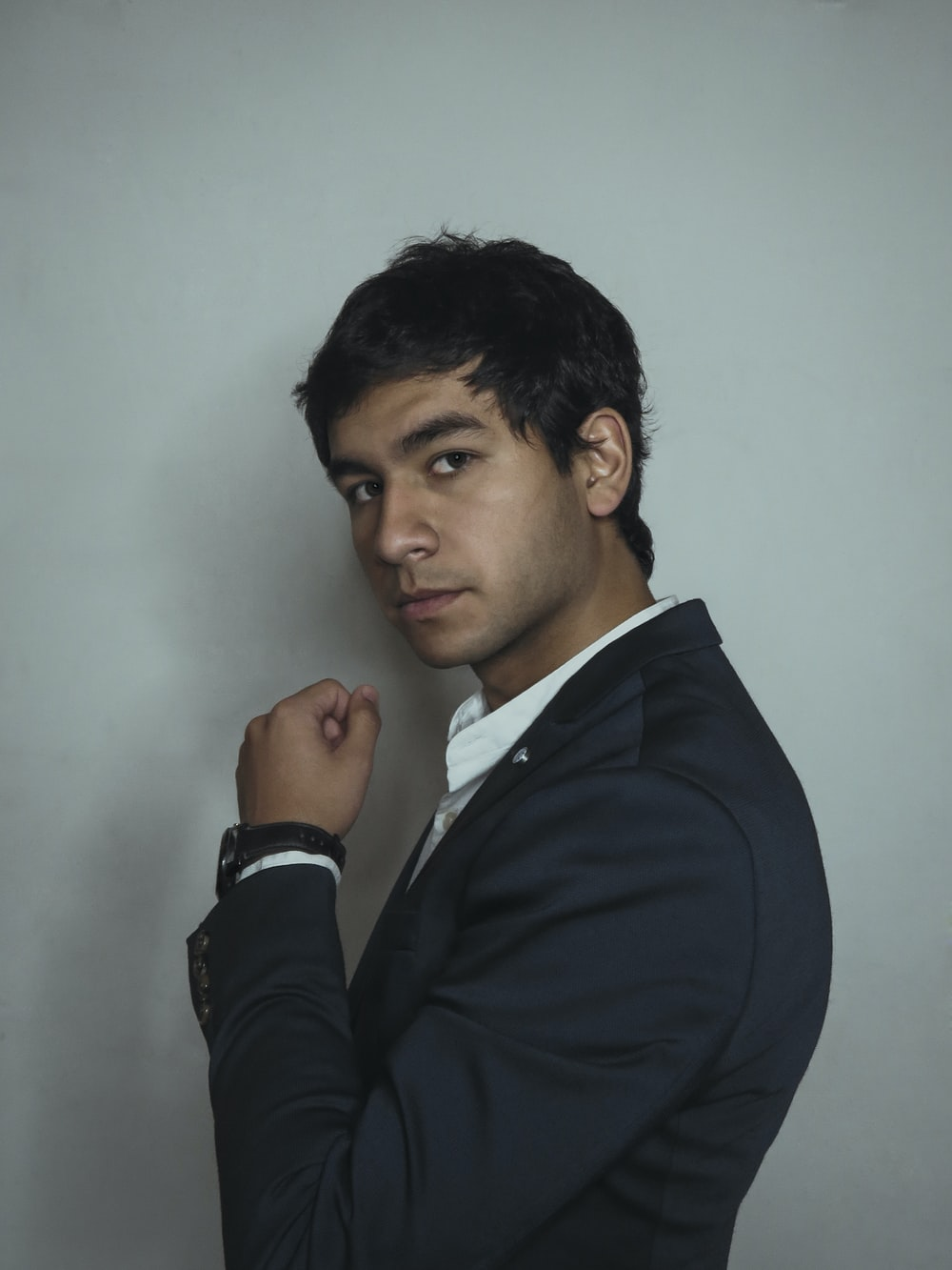 man in black suit beside wall