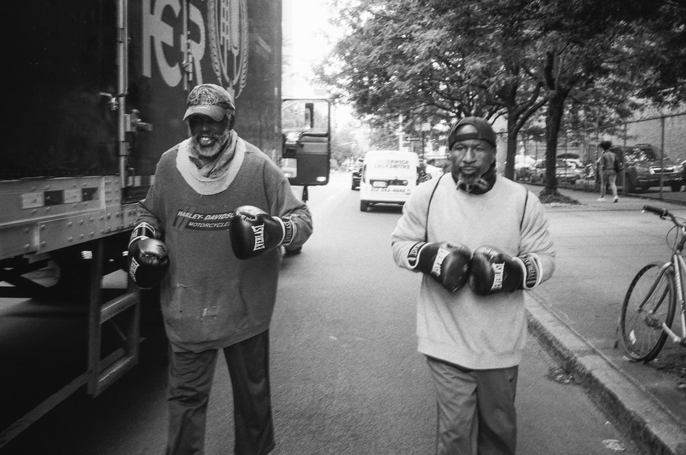 two men wearing boxing gloves walking at the side of the road beside truck