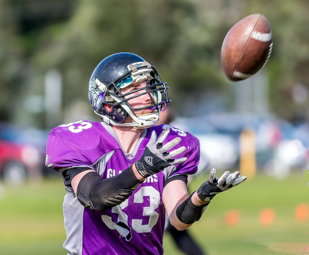 time-lapse photography of a football player catching a ball