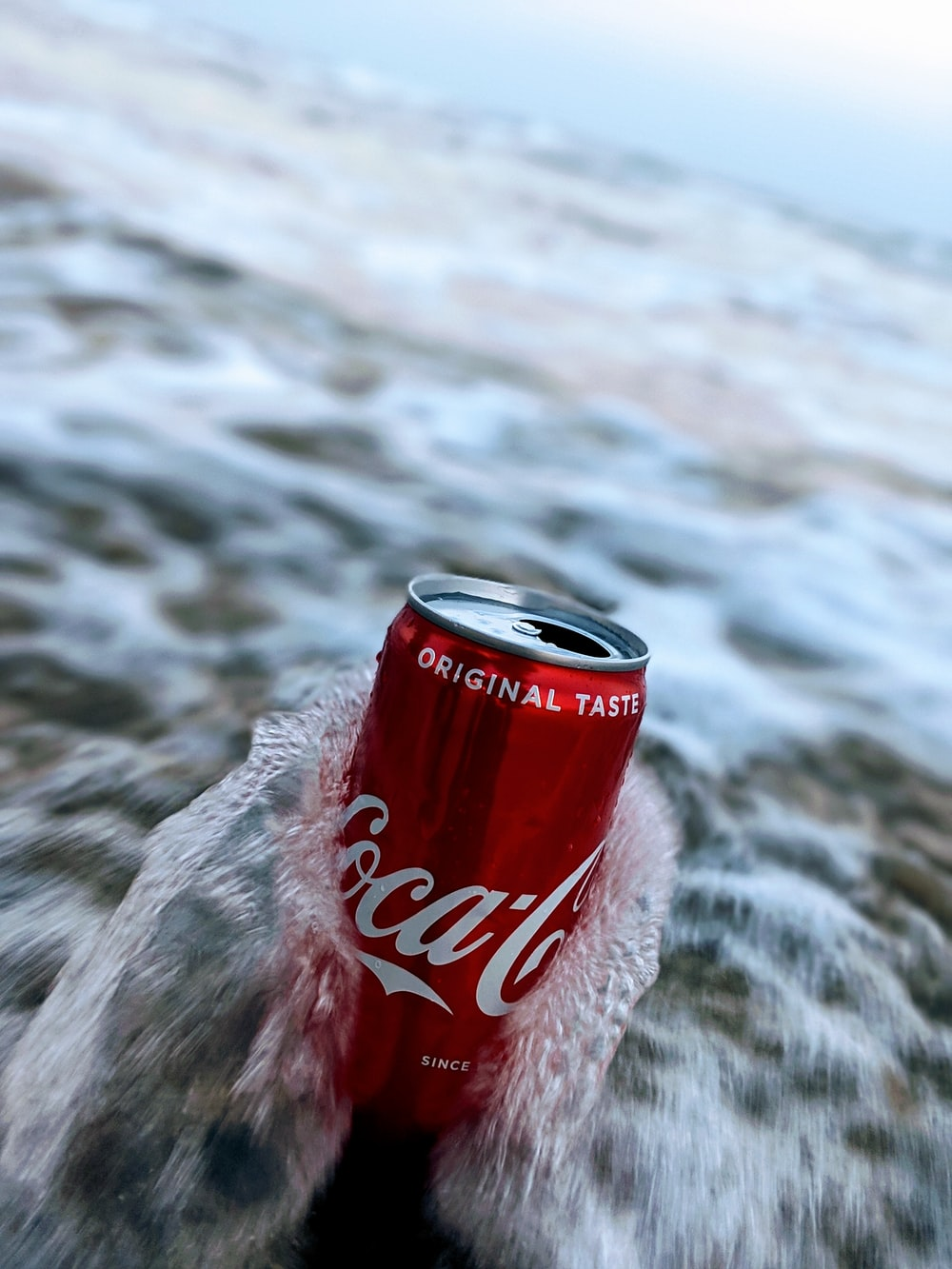 selective focus photography of wave splashing on red Coca-Cola can