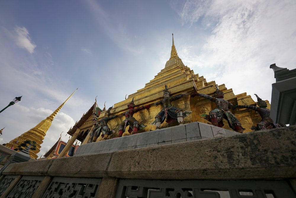 yellow temple under white and blue skies during daytime