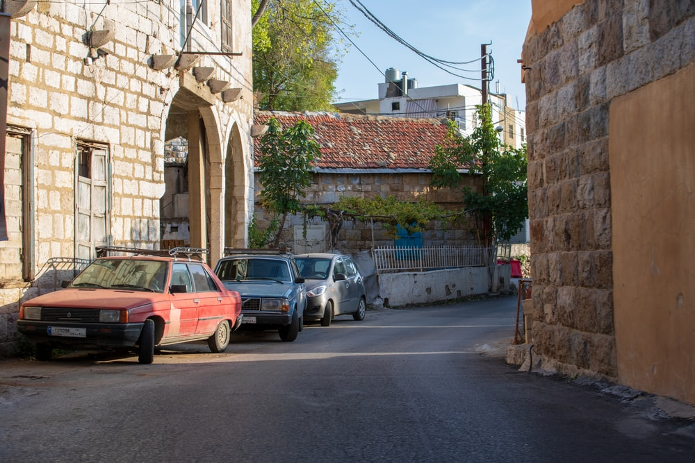 cars parked at the side of the road beside building during day