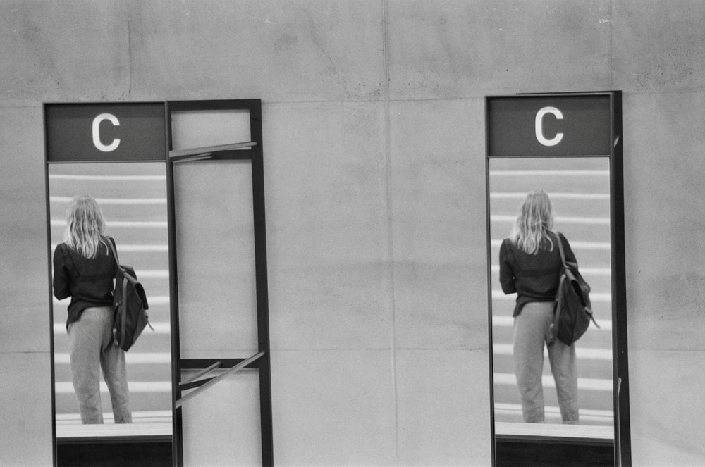 grayscale photography of woman holding backpack