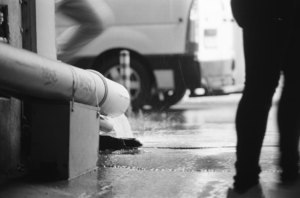 grayscale photography of water pouring from a pipe