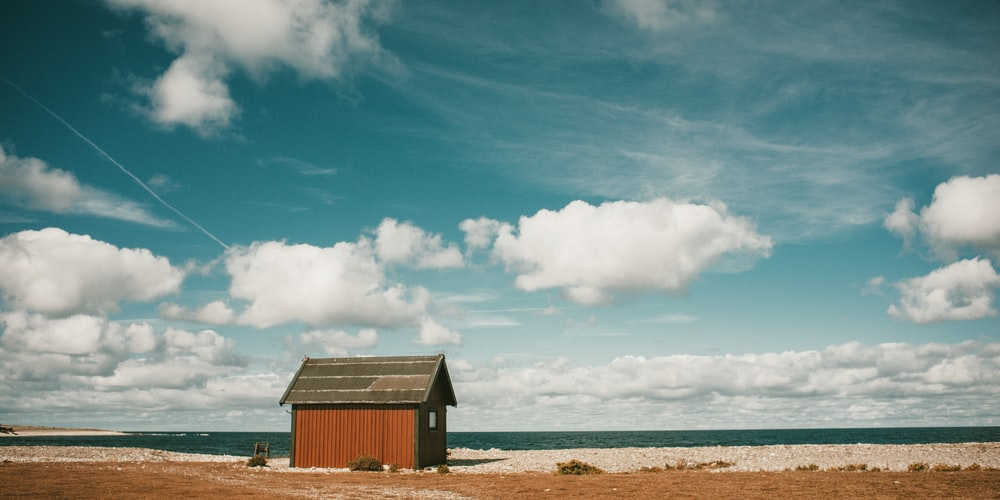 brown wooden house near seashore under white and blue skies during daytime