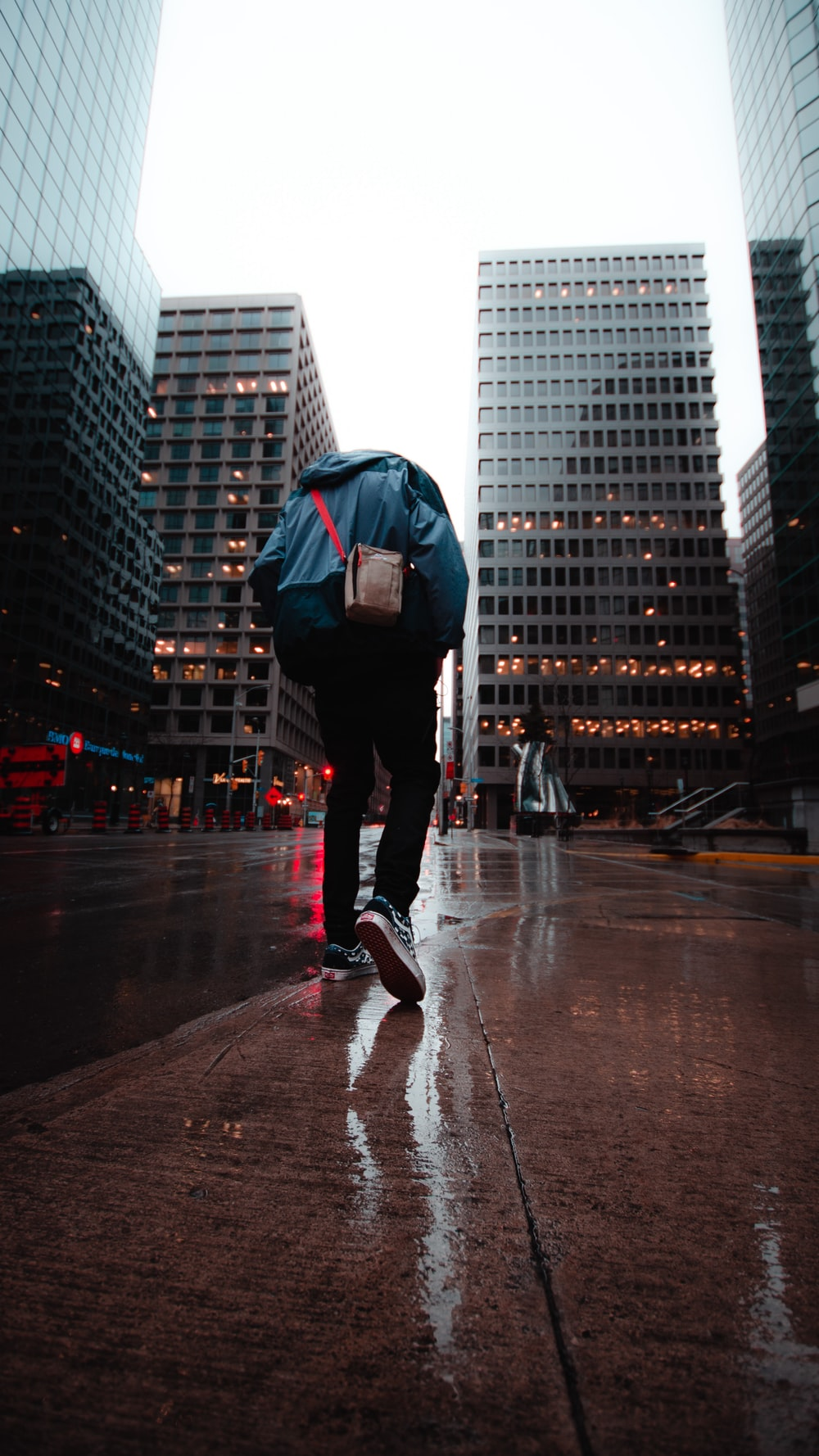 person walking on road near buildings during day