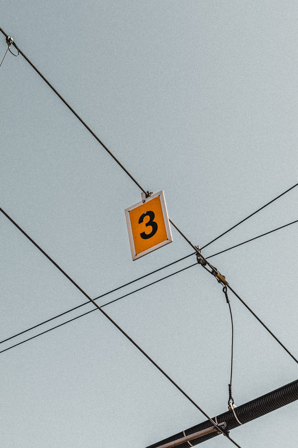 yellow 3 signboard hanging from cable