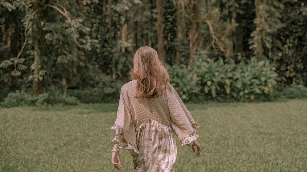 woman wearing beige dress standing on green grass