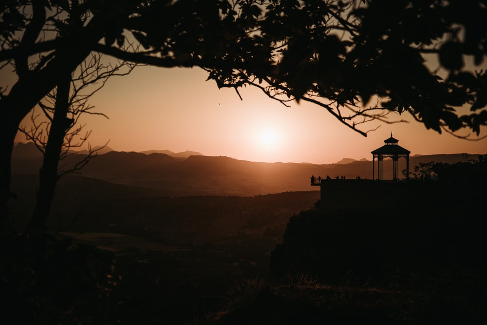 brown gazebo beside mountain during golden hour