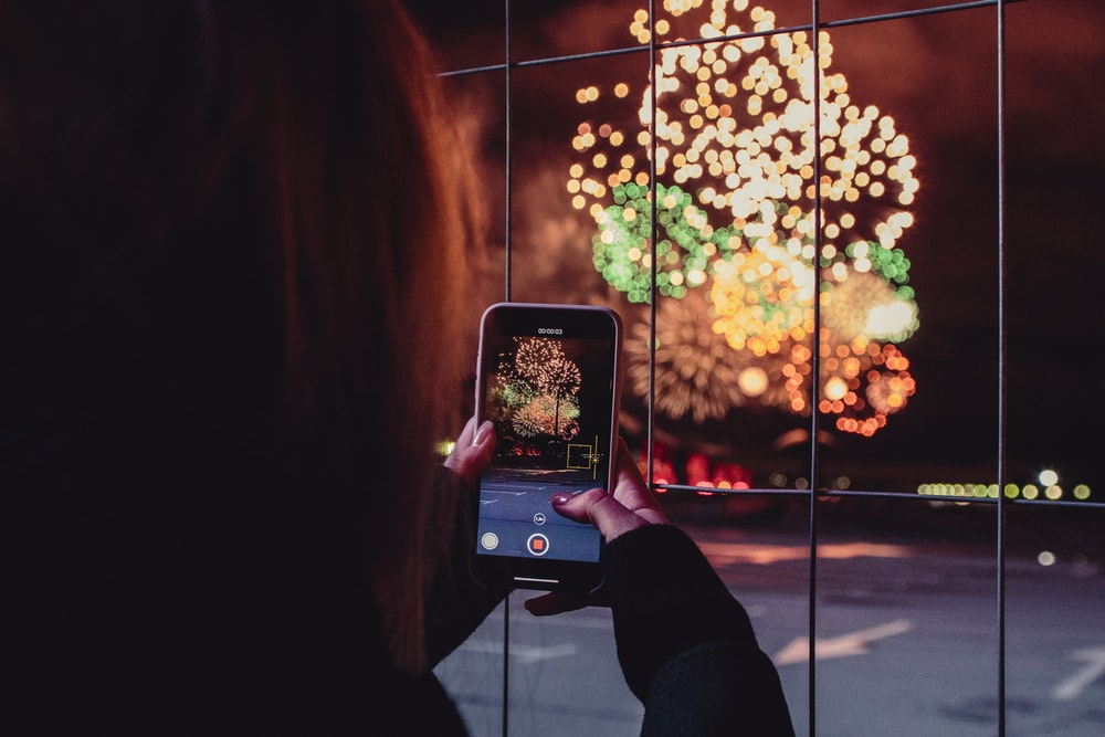 woman taking a picture of fireworks during night