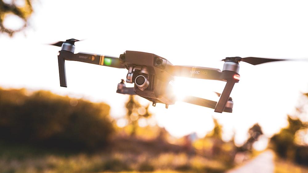 black drone flies under clear sky