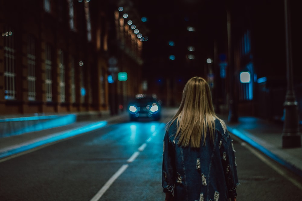 woman standing on road at night