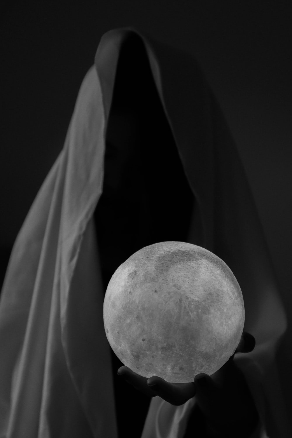 grayscale photo of person holding ball