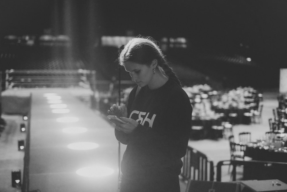 woman using smartphone grayscale photo