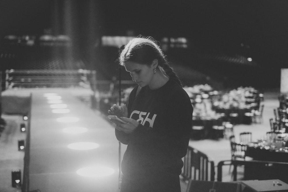 woman using smartphone grayscale photo