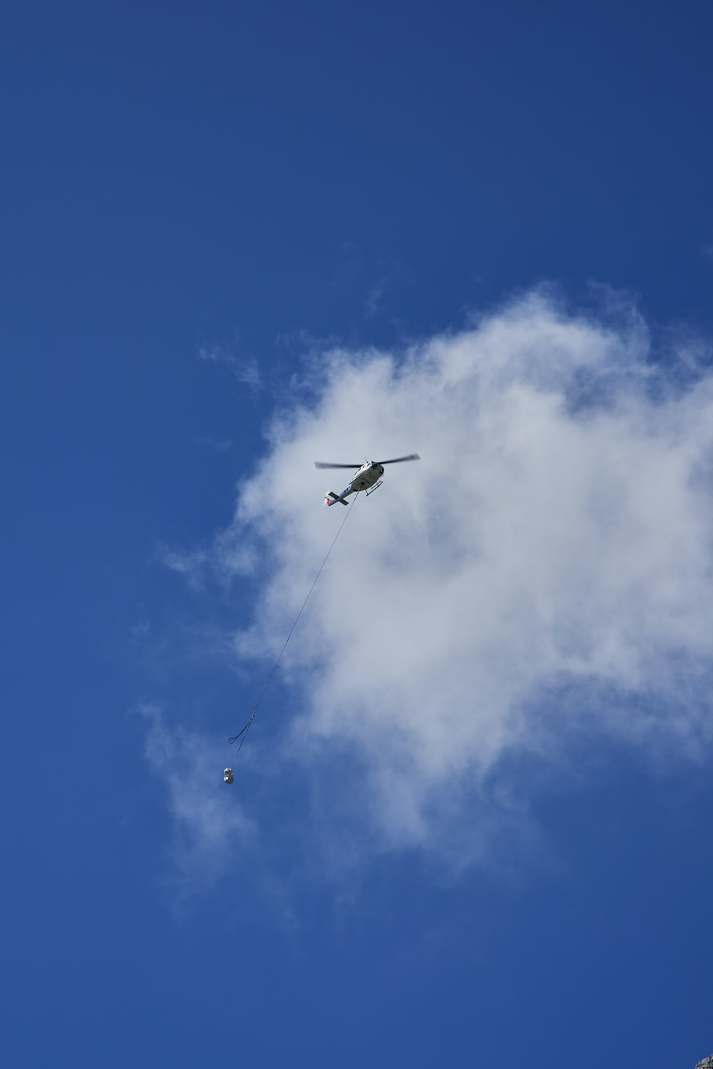 white helicopter under white clouds