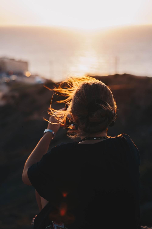 woman in black shirt facing sunset