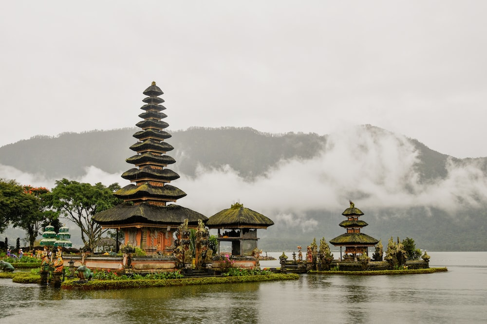green and red pagoda temples by body of water under white skies