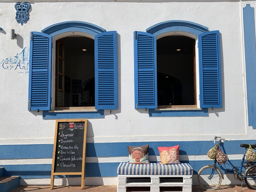 two multicolored throw pillows on bench near bike parking on white and blue wall showing open blue wooden windows