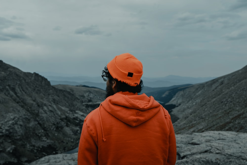 person in orange cap and jacket by mountain slopes
