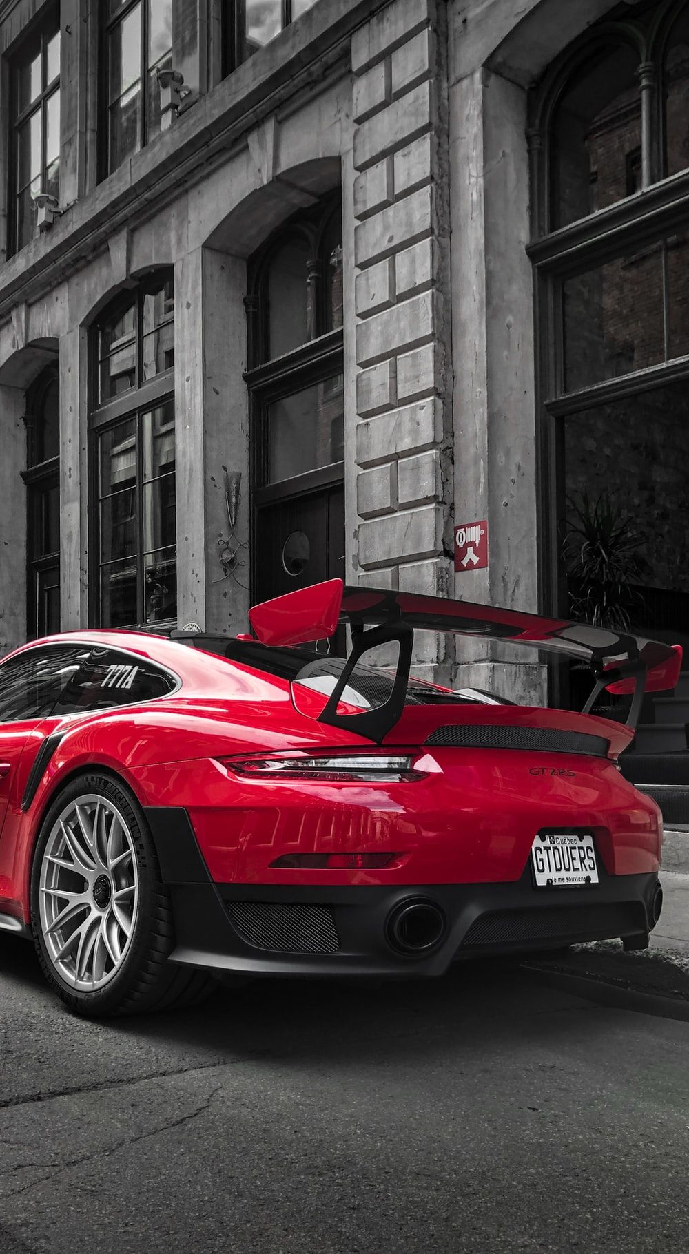 selective color photography of red Porsche sports car parked at roadside