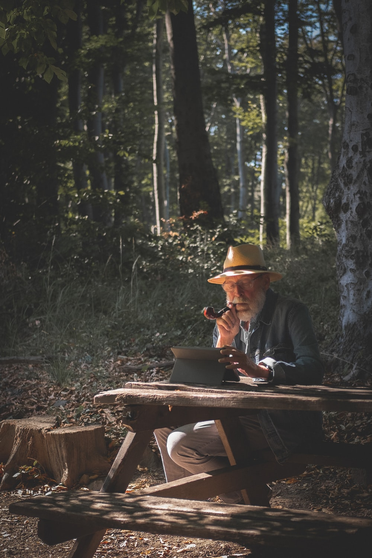 man sitting on picnic table smoking outdoors