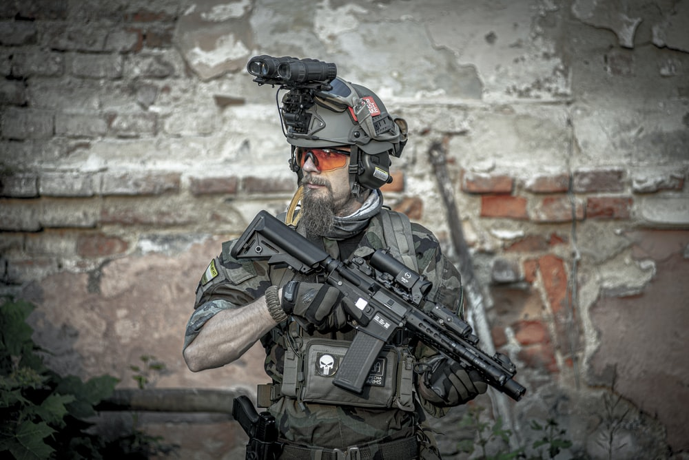soldier man holding assault rifle while standing near building