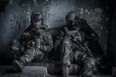 two officers sitting on sofa military zoom background
