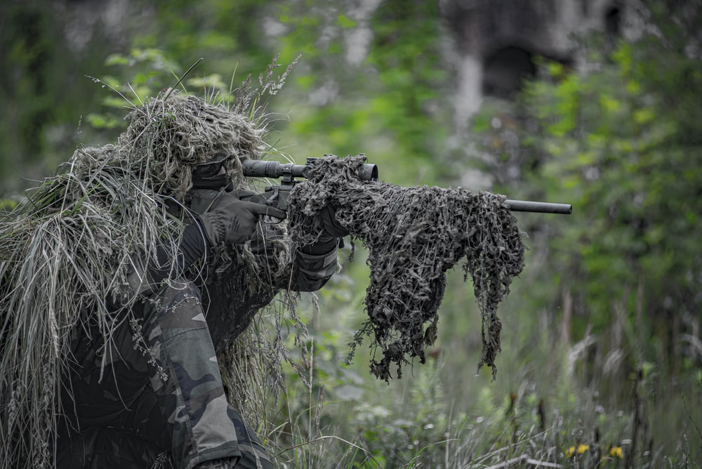 sniper wearing a ghillie in selective focus photography