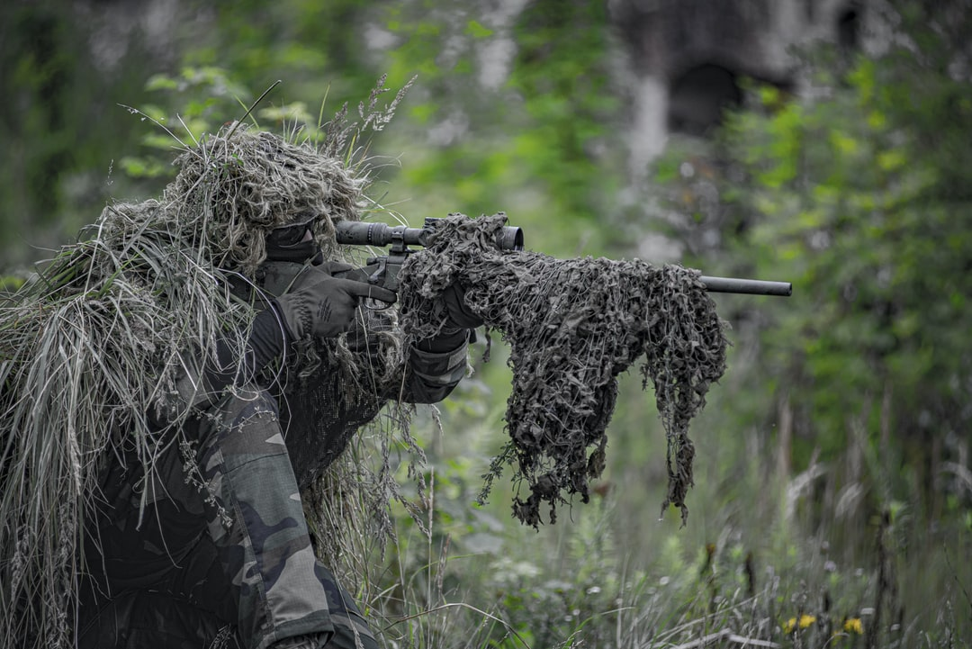 Airsoft sniper, waiting and aiming, player in camouflage