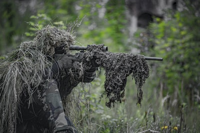 sniper wearing a ghillie in selective focus photography military zoom background