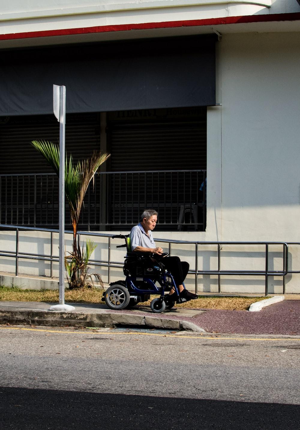 man riding wheelchair at roadside during daytime