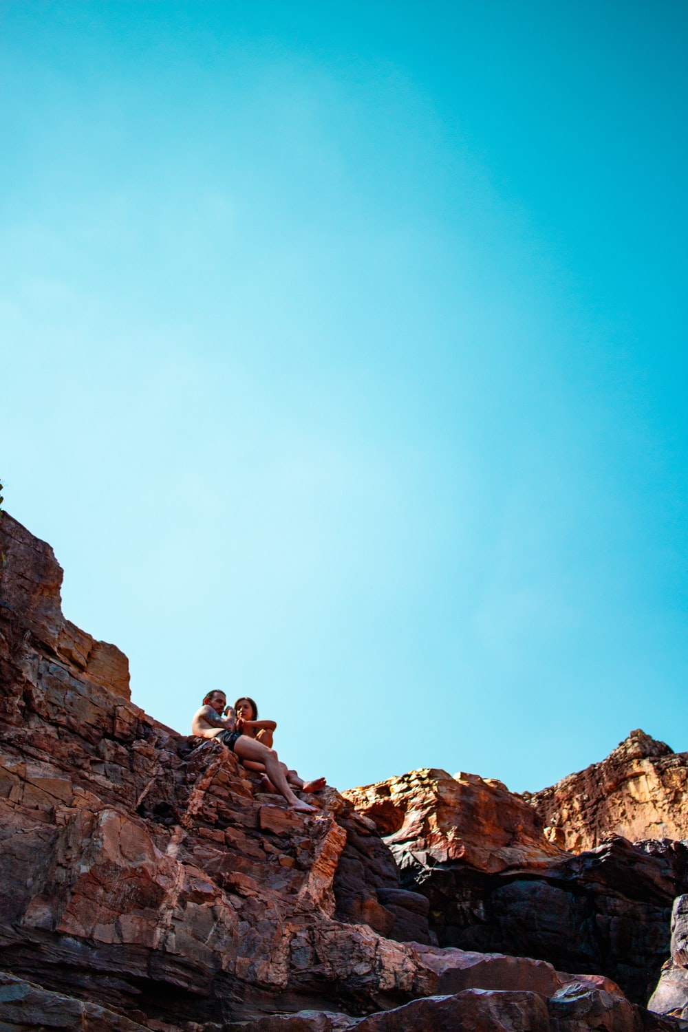 two person sitting on peak at daytime